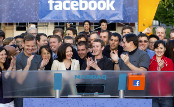 Mark Zuckerberg, chief executive officer of Facebook Inc., center, Sheryl Sandberg, chief operating officer of Facebook, center left, and Robert Greifeld, chief executive officer of Nasdaq OMX Group Inc., center right, applaud after remotely ring the opening bell for trading at the Nasdaq MarketSite from the Facebook campus in Menlo Park, California, U.S., on Friday, May 18, 2012. Facebook Inc. is set to start trading today after a record initial public offering that made the social network more costly than almost every company in the Standard & Poor's 500 Index. Photographer: Zef Nikolla/Facebook via Bloomberg